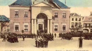 koloniale militairen defileren op marktplein